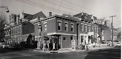 Students congregate at the VMC bookstore, formerly Bob's Bar. The back of the Cathedral can be seen in the upper left.