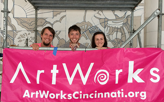 Chris, Jacob, and Karen pose on the scaffolding in front of a detailed section of the mural Karen is working on inside the Cincinnati Justice Center.