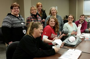 Part of the ministry group with clients of Employment Connections preparing bags to become plarn.