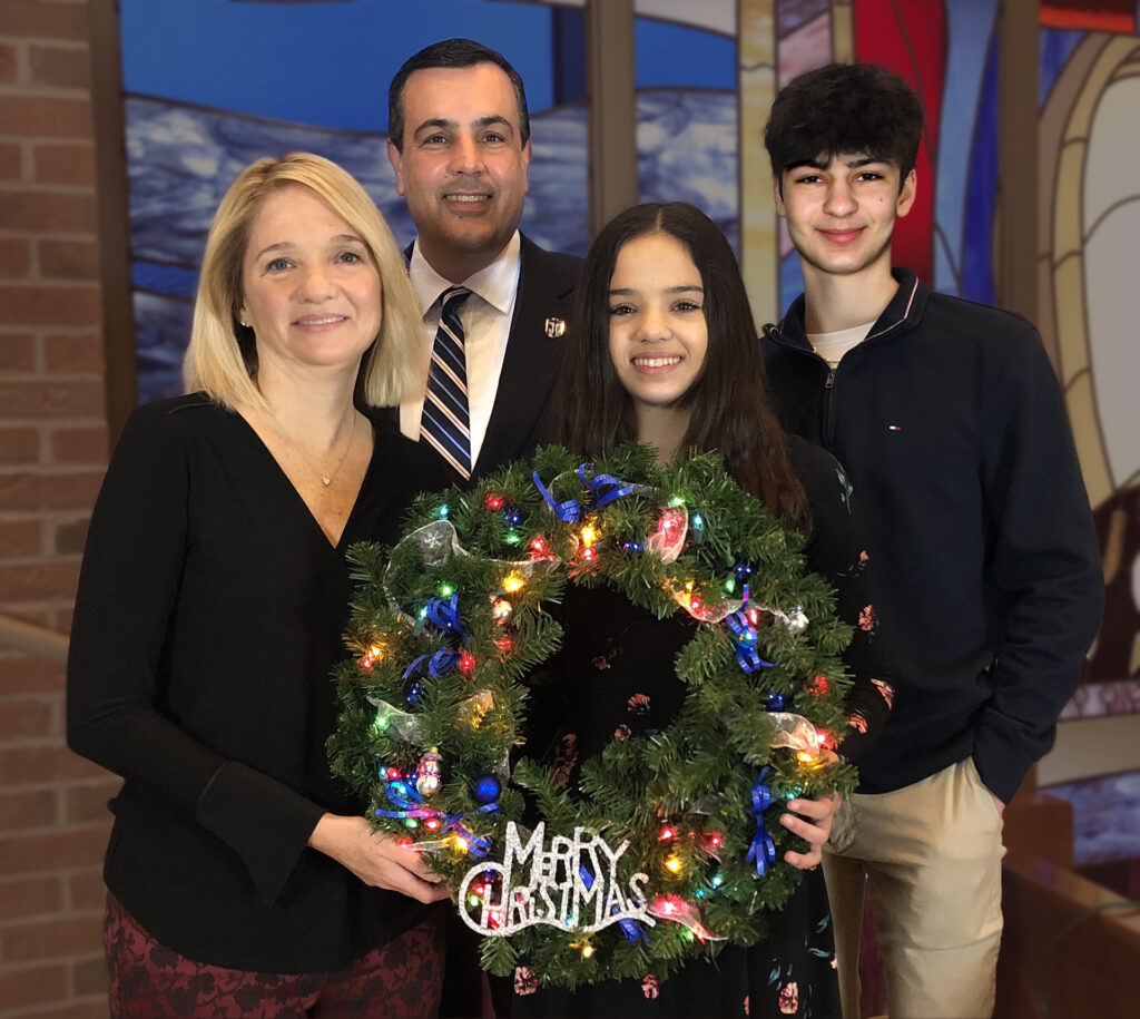 family smiling holding wreath