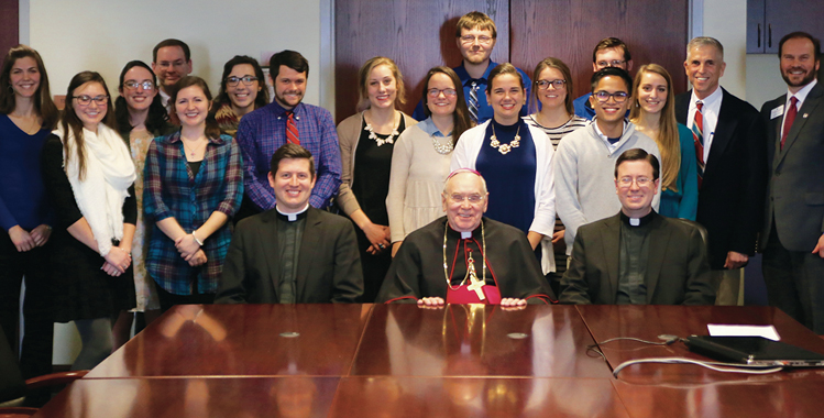 TMC students who attended SEEK 2017 met with Bishop Roger Foys to describe their experiences and how they plan to continue to be catalysts for keeping Catholic Identity a strong part of a Thomas More College education. From left to right are Professor Caitlin Dwyer, Emilee Urichich '19, Sofie Vietas '19, Marc Neltner '85, Courtney Neltner '17, Hannah Bockweg (NKU student), Greg Warner '17,  Joanna Roessler (dual credit student), Katie Bischoff '17, Joseph Schneider '19, Jenna Willett '19, Caroline Middendorf '19, Ran Liwag '17, Tim McDonald '20, Kristin Klocke '17, Professor Jack Rudnick, and Andrew Cole. Additional attendees not pictured are Gillian Casey '19, Chelsea Doering '18, Kendal Emerson '20, Lydia Fischesser '18, Savannah Frank '17, Evan Harmeling '18, Jacob Hensley '19, Riley Kinsella '18, Chris Loos '19, Bridget Neltner '20, Will Neltner '18, Brooke Schleben '17, Eli Smith, and Maria Syfert '17.